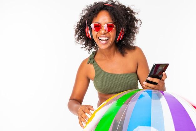 Ładna afrykańska kobieta w strój kąpielowy stoi z dużą kolorową gumową piłką, słucha muzyki z odosobnionymi słuchawkami