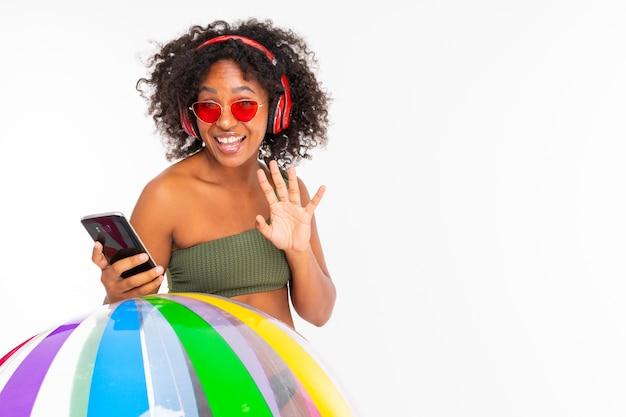 Ładna afrykańska kobieta w strojach kąpielowych stoi z dużą kolorową gumową piłką, słucha muzyki przez słuchawki i robi selfie na białym tle