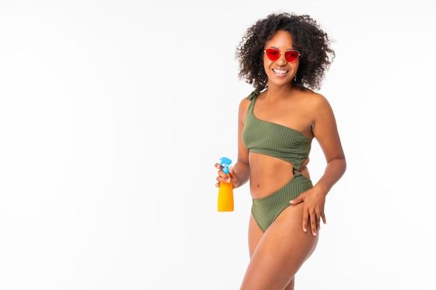 Ładna afrykańska kobieta w swimsuit z spay puszką i uśmiechami odizolowywającymi