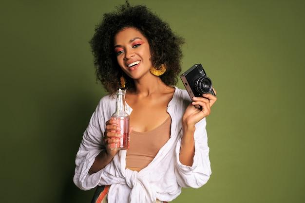 Ładna afrykańska kobieta ze stawianiem fryzury afro, picie lemoniady ze słomy. letni styl. jasny makijaż.