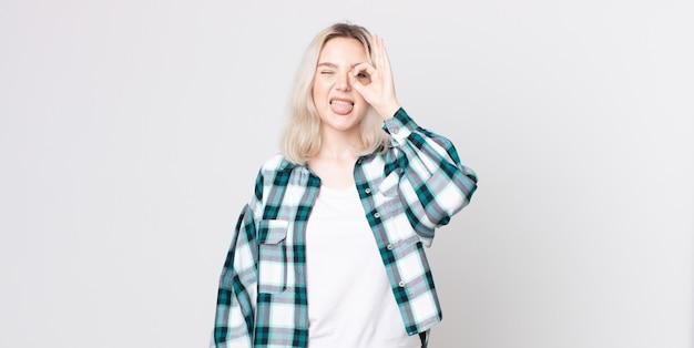 Ładna albinoska uśmiechnięta radośnie ze śmieszną miną, żartująca i patrząca przez wizjer, szpiegująca sekrety