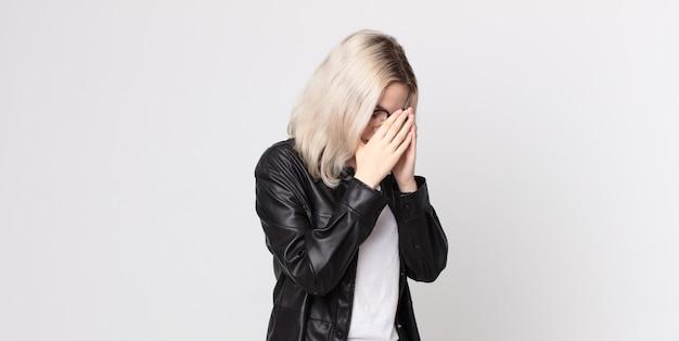 Ładna albinoska zakrywająca oczy dłońmi ze smutnym, sfrustrowanym wyrazem rozpaczy, płaczu, widoku z boku