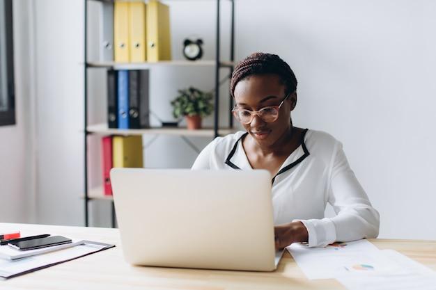 Ładna amerykanin afrykańskiego pochodzenia biznesowa kobieta pracuje na laptopie w biurze