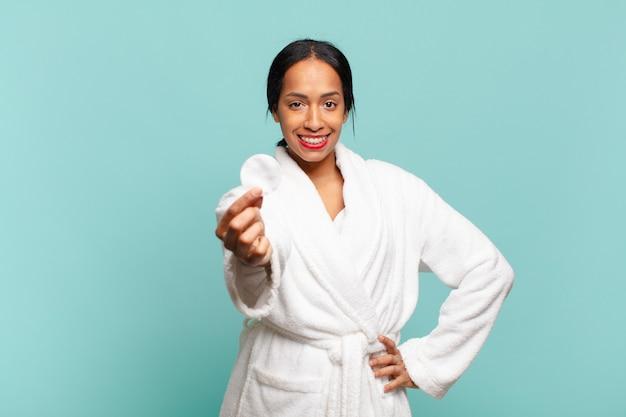 Ładna amerykańska kobieta z dumnym i szczęśliwym wyrazem twarzy pokazująca bawełnę do makijażu