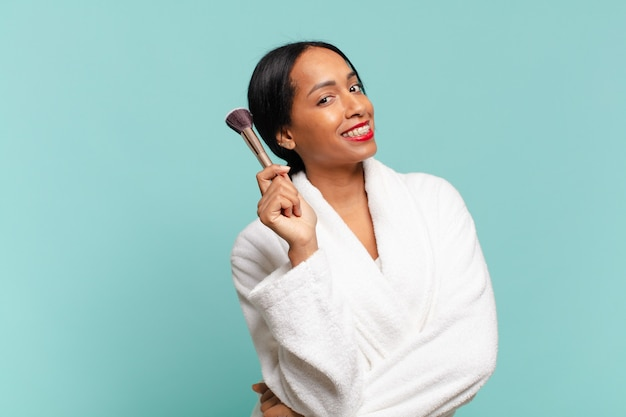 Ładna amerykańska kobieta z dumnym i szczęśliwym wyrazem twarzy pokazująca pędzel do makijażu