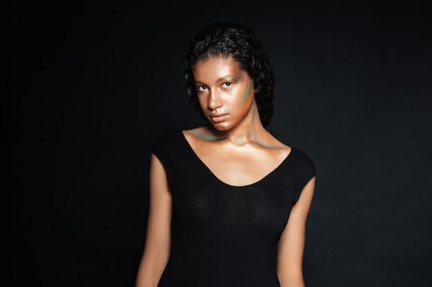 Ładna amerykańska młoda kobieta z lśniącym makijażem, stojąca na czarno