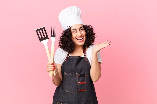 Ładna arabka czuje się szczęśliwa i zdumiona czymś niewiarygodnym. koncepcja szefa kuchni grilla