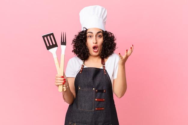 Ładna arabka czuje się w szoku i zaskoczeniu. koncepcja szefa kuchni grilla