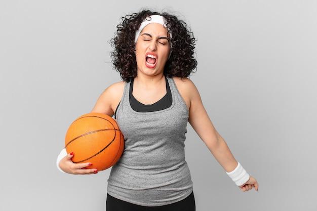 Ładna arabka krzycząca agresywnie, wyglądająca na bardzo rozgniewaną i trzymająca piłkę do koszykówki. koncepcja sportu
