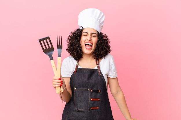 Ładna arabka krzycząca agresywnie, wyglądająca na bardzo rozgniewaną. koncepcja szefa kuchni grilla