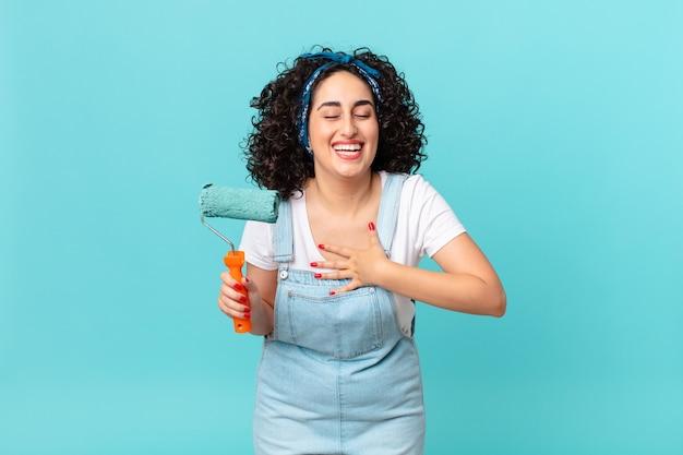 Ładna arabka śmiejąca się głośno z jakiegoś zabawnego żartu. koncepcja malowania domu