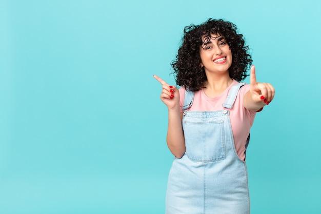 Ładna arabka uśmiecha się dumnie i pewnie robi numer jeden