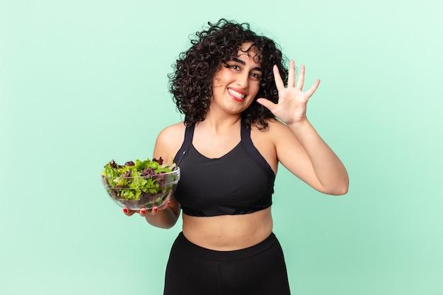 Ładna arabka uśmiechnięta i wyglądająca przyjaźnie, pokazująca numer pięć i trzymająca sałatkę. koncepcja diety