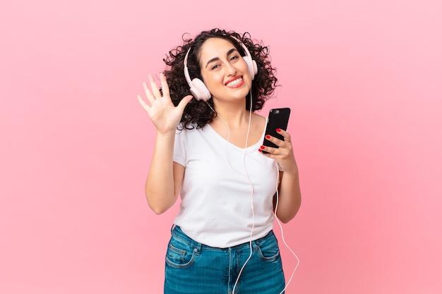 Ładna arabka uśmiechnięta i wyglądająca przyjaźnie, pokazująca numer pięć ze słuchawkami i smartfonem