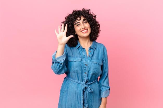 Ładna arabka uśmiechnięta i wyglądająca przyjaźnie, pokazująca numer pięć