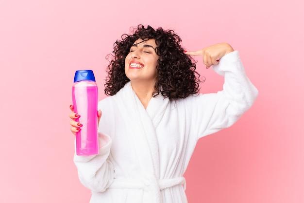 Ładna arabka w szlafroku i trzymająca butelkę szamponu