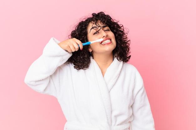 Ładna arabka w szlafroku i używająca szczoteczki do zębów