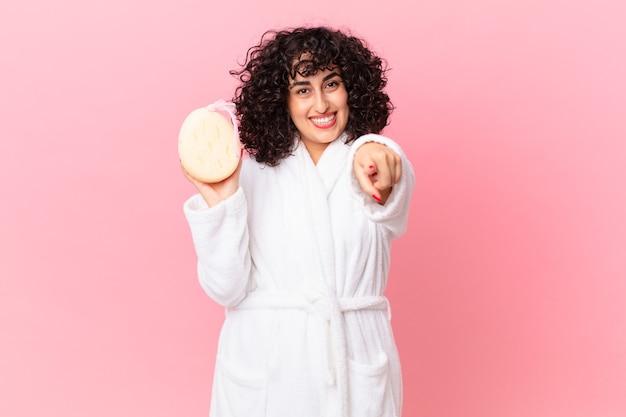 Ładna arabka wskazująca na kamerę, która wybiera cię w szlafroku i trzyma gąbkę