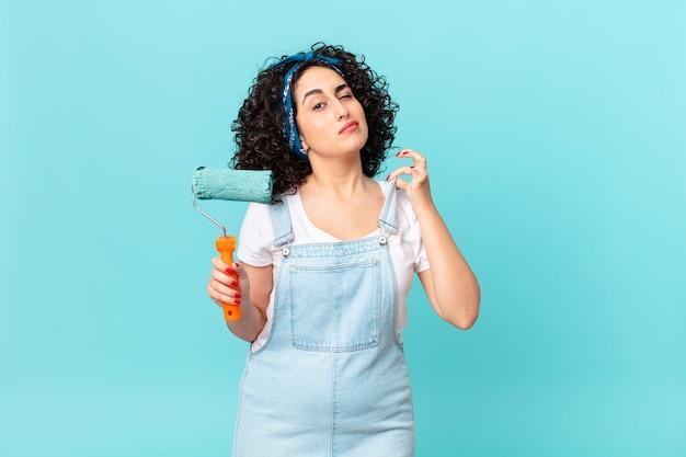 Ładna arabka wyglądająca na arogancką, odnoszącą sukcesy, pozytywną i dumną. koncepcja malowania domu