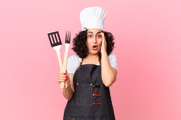 Ładna arabka wyglądająca na szczęśliwą, zdumioną i zdziwioną. koncepcja szefa kuchni grilla