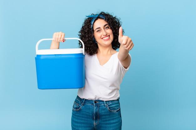 Ładna arabska kobieta czuje się dumna, uśmiecha się pozytywnie z kciukami do góry i trzyma przenośną lodówkę