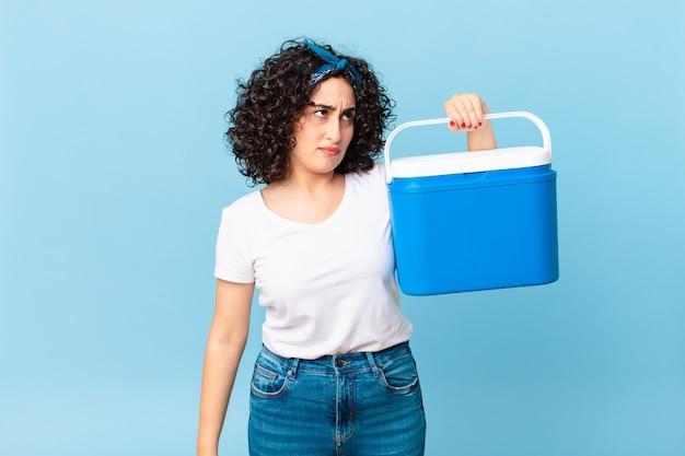 Ładna arabska kobieta czuje się smutna, zdenerwowana lub zła, patrzy w bok i trzyma przenośną lodówkę