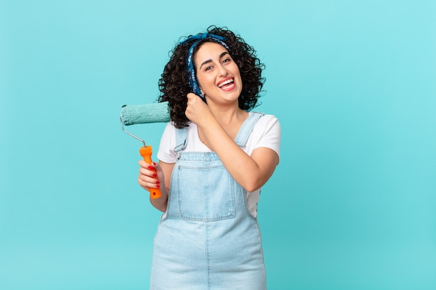 Ładna arabska kobieta czuje się szczęśliwa i staje przed wyzwaniem lub świętuje. koncepcja malowania domu
