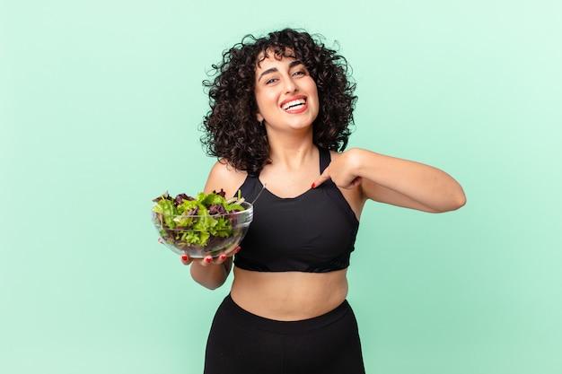 Ładna arabska kobieta czuje się szczęśliwa i wskazuje na siebie z podekscytowaną i trzymającą sałatkę. koncepcja diety