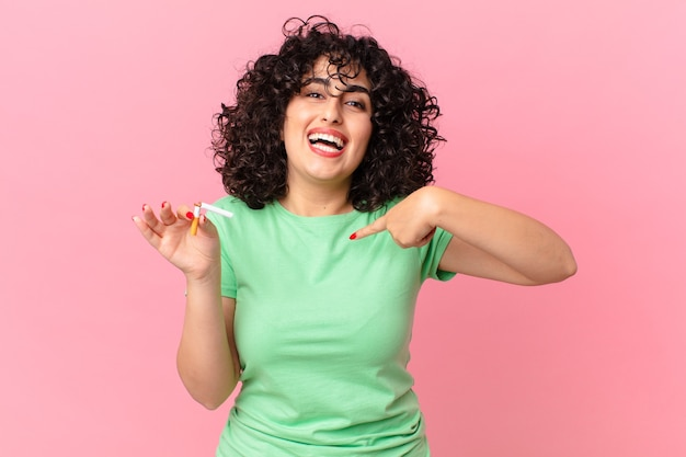 Ładna arabska kobieta czuje się szczęśliwa i wskazuje na siebie z podekscytowaniem. brak koncepcji palenia