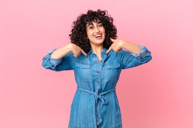 Ładna arabska kobieta czuje się szczęśliwa i wskazuje na siebie z podekscytowaniem