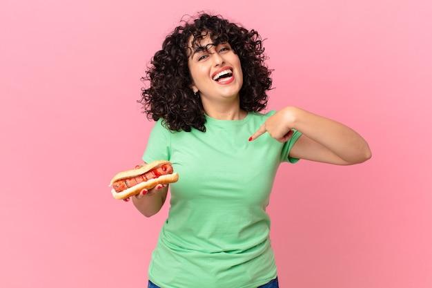 Ładna arabska kobieta czuje się szczęśliwa i wskazuje na siebie z podekscytowanym i trzymającym hot doga