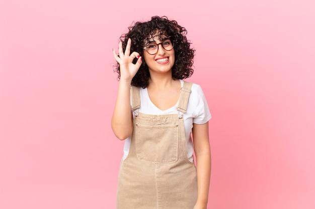 Ładna arabska kobieta czuje się szczęśliwa, pokazując aprobatę dobrym gestem