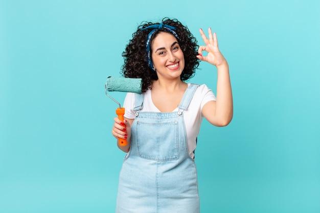 Ładna arabska kobieta czuje się szczęśliwa, pokazując aprobatę w porządku gestem. koncepcja malowania domu