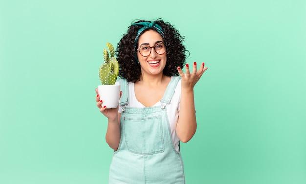 Ładna arabska kobieta czuje się szczęśliwa, zaskoczona, gdy zdaje sobie sprawę z rozwiązania lub pomysłu i trzyma doniczkowego kaktusa