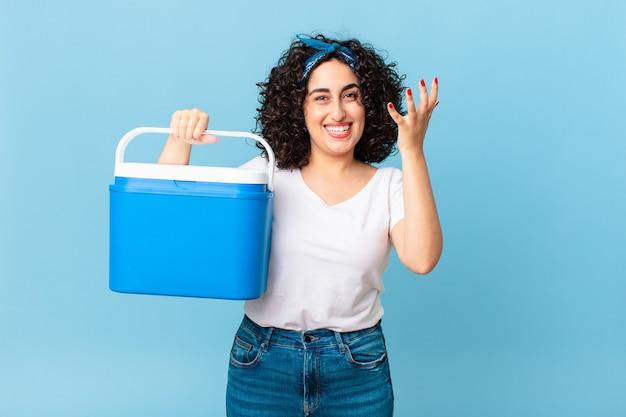 Ładna arabska kobieta czuje się szczęśliwa, zaskoczona, gdy zdaje sobie sprawę z rozwiązania lub pomysłu i trzyma przenośną lodówkę