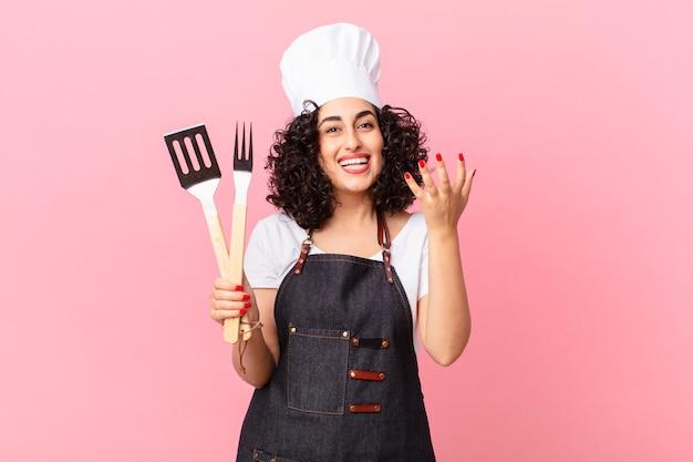 Ładna arabska kobieta czuje się szczęśliwa, zaskoczona, gdy zdaje sobie sprawę z rozwiązania lub pomysłu. koncepcja szefa kuchni grilla