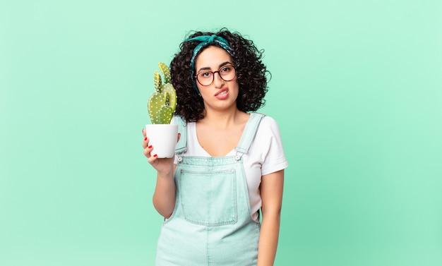 Ładna arabska kobieta czuje się zakłopotana i zdezorientowana i trzyma doniczkowego kaktusa
