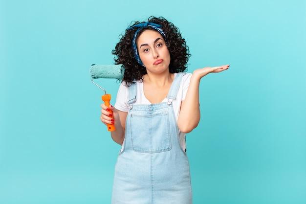 Ładna arabska kobieta czuje się zakłopotana, zdezorientowana i wątpi. koncepcja malowania domu