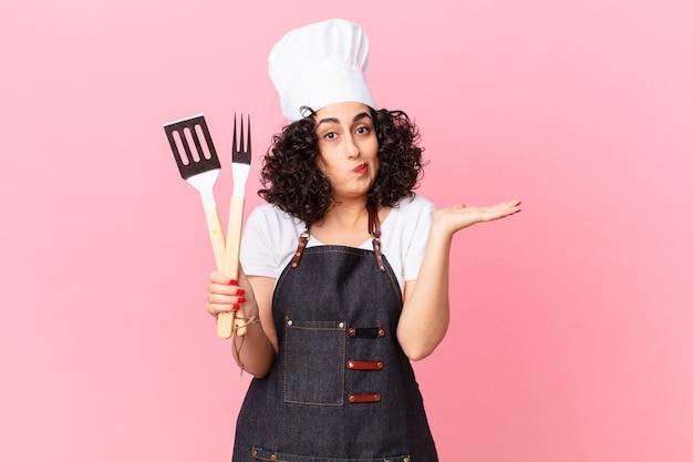 Ładna arabska kobieta czuje się zakłopotana, zdezorientowana i wątpi. koncepcja szefa kuchni grilla
