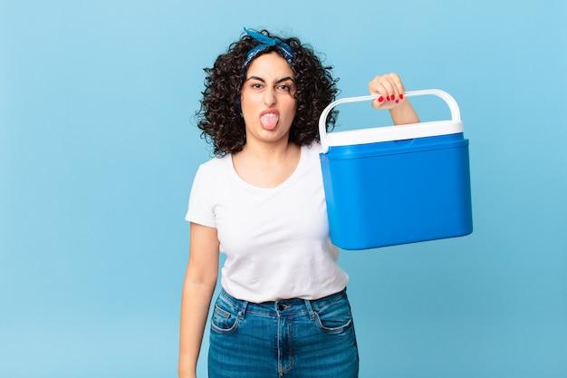 Ładna arabska kobieta czuje się zdegustowana i zirytowana, wysuwa język i trzyma przenośną lodówkę