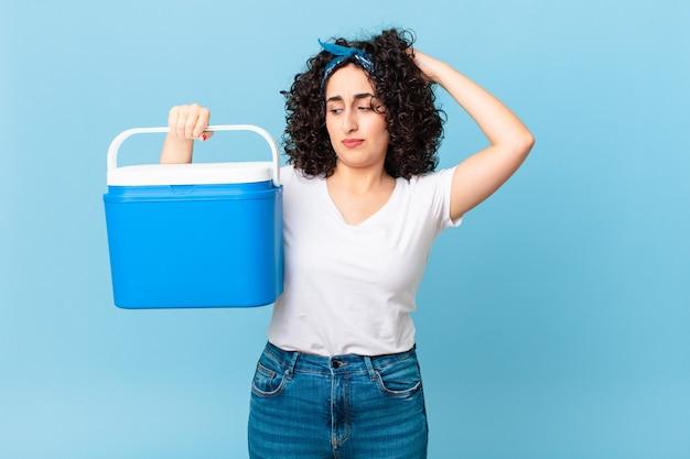 Ładna arabska kobieta czuje się zdezorientowana i zdezorientowana, drapiąc się po głowie i trzymając przenośną lodówkę