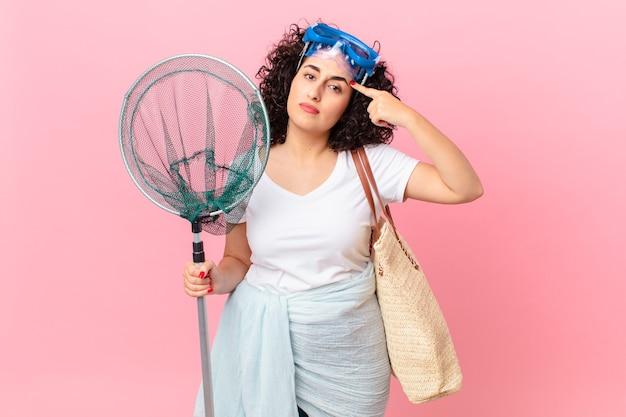 Ładna arabska kobieta czuje się zdezorientowana i zdezorientowana, pokazując, że jesteś szalony z goglami. koncepcja rybaka