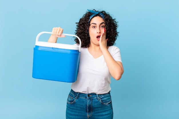 Ładna arabska kobieta czuje się zszokowana i przestraszona i trzyma przenośną lodówkę