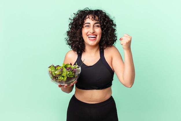 Ładna arabska kobieta czuje się zszokowana, śmieje się i świętuje sukces i trzyma sałatkę. koncepcja diety