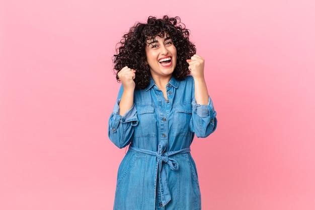Ładna arabska kobieta czuje się zszokowana, śmieje się i świętuje sukces