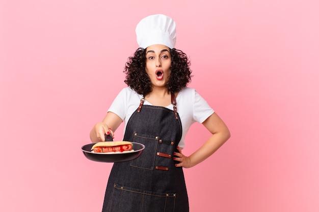 Ładna arabska kobieta grillująca szef kuchni przygotowująca hot dogi