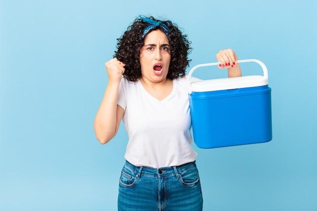 Ładna arabska kobieta krzycząca agresywnie z gniewnym wyrazem twarzy i trzymająca przenośną lodówkę
