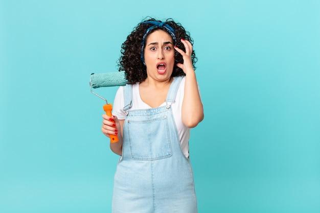 Ładna arabska kobieta krzyczy z rękami w powietrzu. koncepcja malowania domu