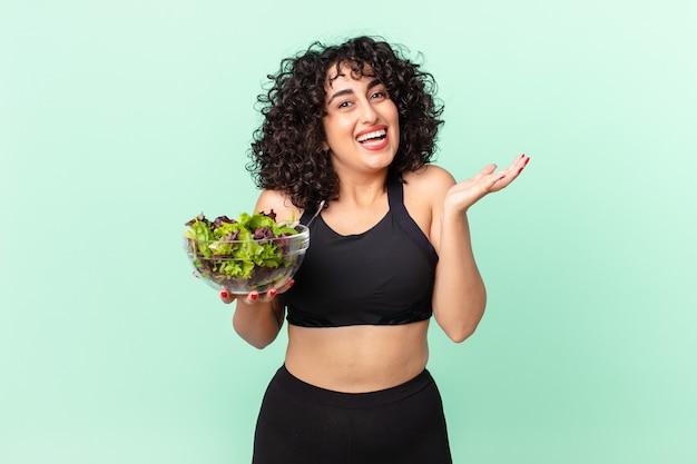 Ładna arabska kobieta, która czuje się szczęśliwa i zdumiona czymś niewiarygodnym i trzyma sałatkę. koncepcja diety