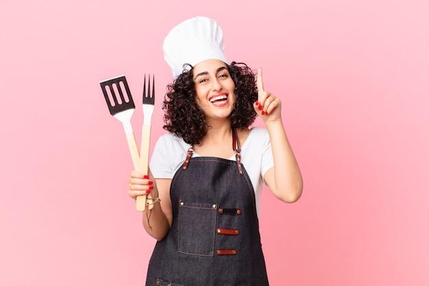 Ładna arabska kobieta, która po zrealizowaniu pomysłu czuje się jak szczęśliwy i podekscytowany geniusz. koncepcja szefa kuchni grilla